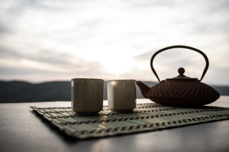 Tea concept. Japanese tea ceremony culture east beverage. Teapot and cups on table with bamboo leaves on sunset royalty free stock image