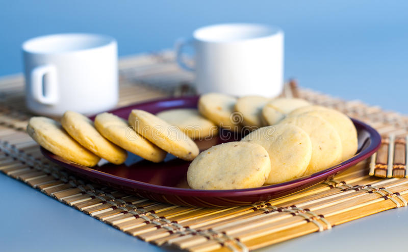 Tea with Cookies. Two teacups with many cookies or biscuits in a brown plat with a table mat royalty free stock photos