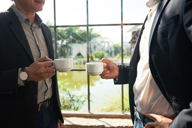 Tea with coworker. Cropped image of business partners drinking tea at big window stock photo
