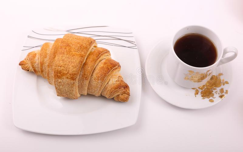Tea with croissant. Croissant with cup of tea on modern black dish over white background royalty free stock photos