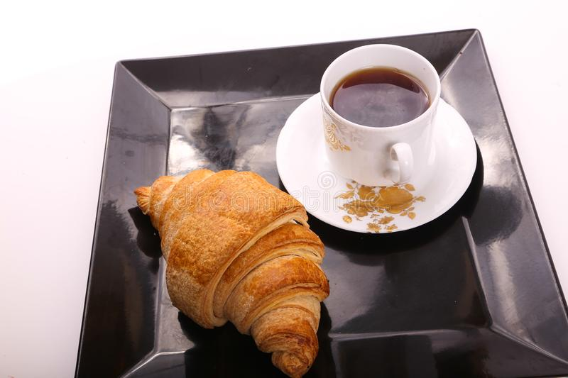 Tea with croissant. Croissant with cup of tea on modern black dish over white background stock photos
