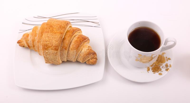 Tea with croissant. Croissant with cup of tea on modern black dish over white background royalty free stock images