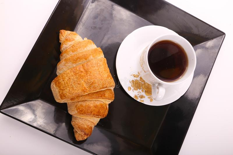 Tea with croissant. Croissant with cup of tea on modern black dish over white background stock photo