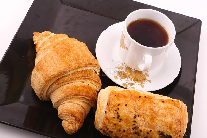 Tea with croissant and paté. Croissant and paté with cup of tea on modern black dish over white background royalty free stock photos