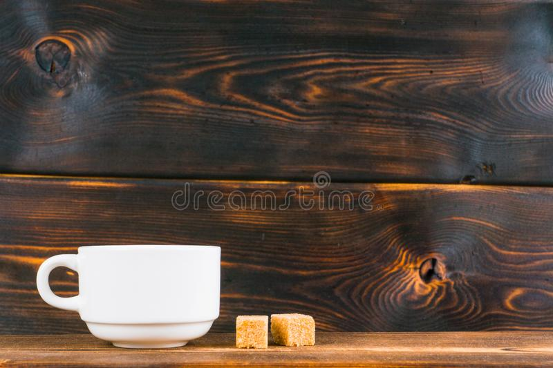 Tea cup and brown sugar on wooden table. Tea cup and brown sugar on rustic wooden table royalty free stock photos