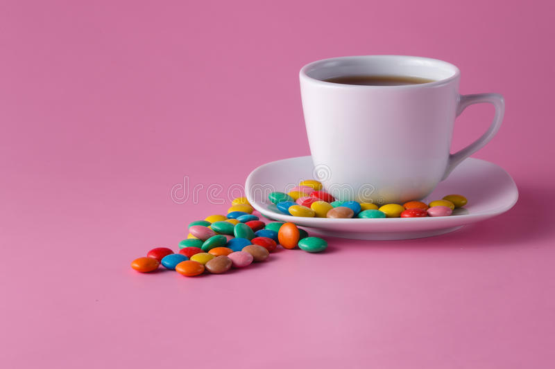 Tea cup with colored sweet dragees on saucer royalty free stock photo