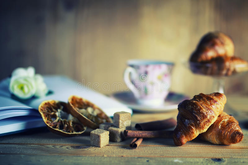 Tea cup croissant book. Small freshly baked croissant and cup of hot flavored tea on the table royalty free stock photography
