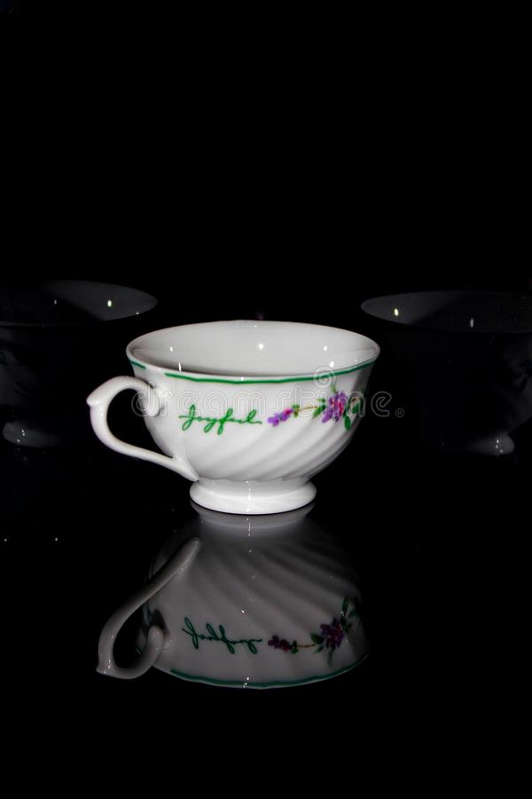 Tea cup in the dark. Picture of tea cup capture in the dark condition therefore it has reflection stock images