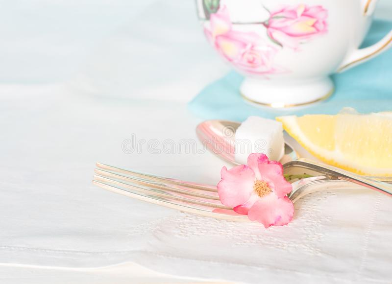 Tea Cup, Fork and Spoon with sugar cube and lemon on white table cloth stock images