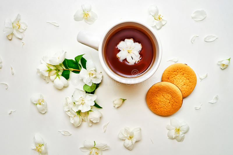 Tea cup with fragrant Jasmine flowers and biscuits in background stock photo