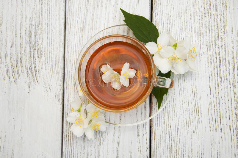 Tea. A cup of jasmine tea with jasmine flowers on a wooden background royalty free stock photo