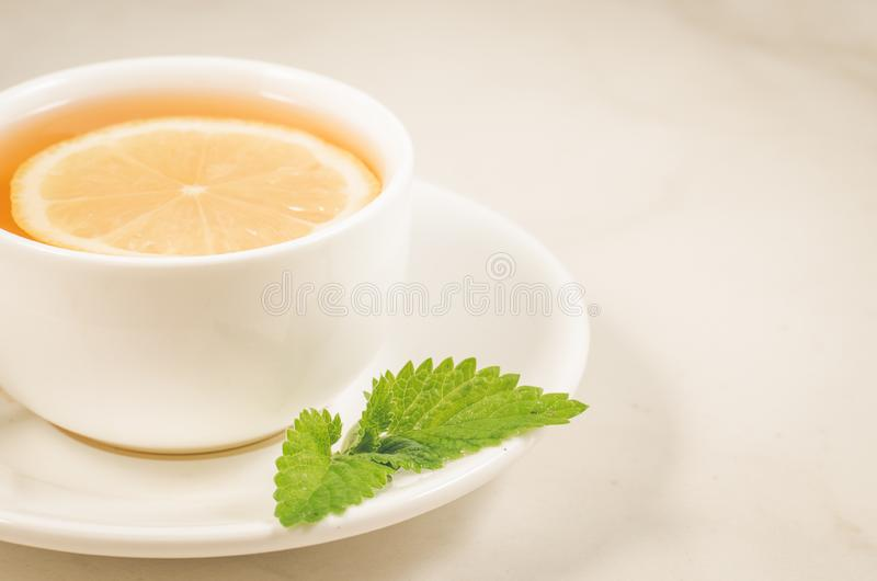 Tea cup with a lemon and mint/tea cup with a lemon and mint on a white marble background closeup. Selective focus. Green drink hot food healthy leaf herb herbal stock photo