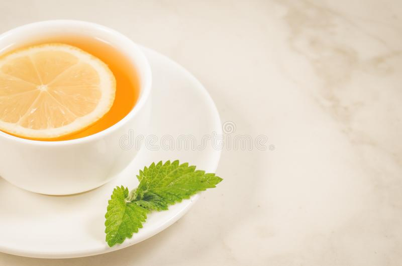 Tea cup with a lemon and mint/tea cup with a lemon and mint on a white marble background. Selective focus and copy space. Green, drink, hot, food, healthy stock photography