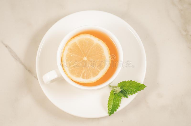 Tea cup with a lemon and mint/tea cup with a lemon and mint on a white marble background, top view. Green, drink, hot, food, healthy, leaf, herb, herbal stock images