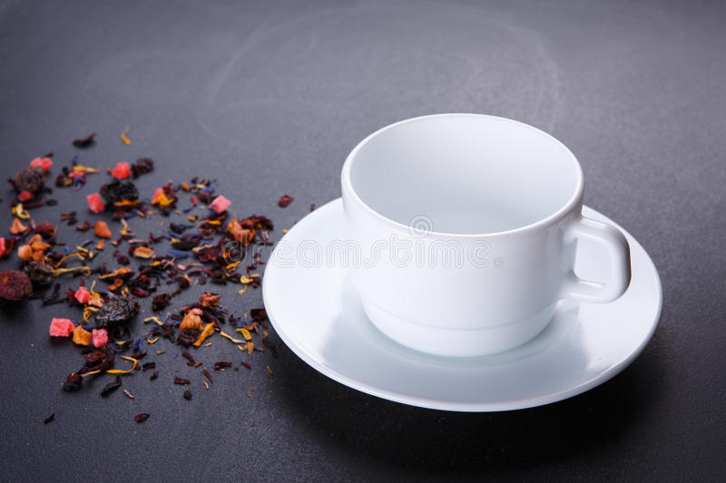 Tea cup with saucer on black background. Mixture herbal floral fruit tea with petals, dry berries and fruits. royalty free stock photos