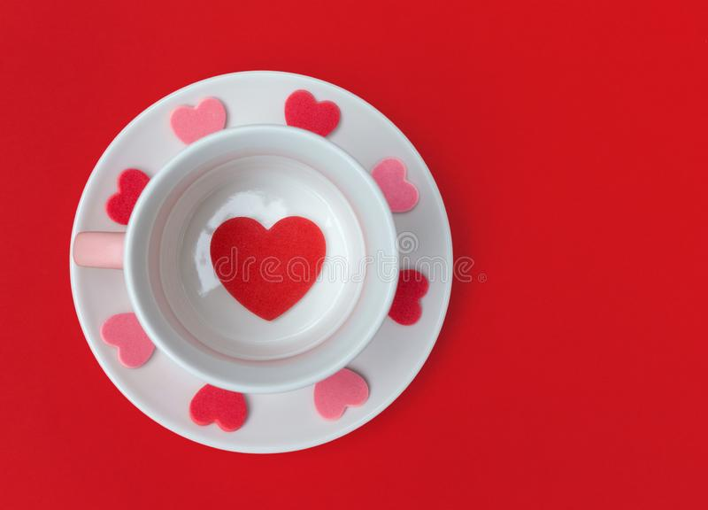 Tea cup and saucer with love hearts on a red background. Flat lay with copy space royalty free stock images