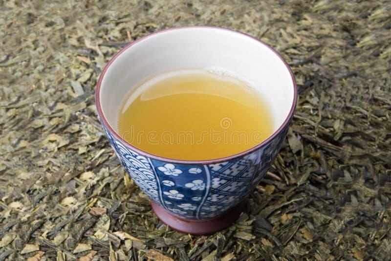 Tea cup on tea leafs stock photos