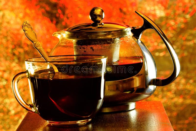 Tea in a Cup and teapot on the background of rainbow lights. Tea is a popular healthy drink obtained by brewing and infusing a. Leaf of a tea Bush royalty free stock photo