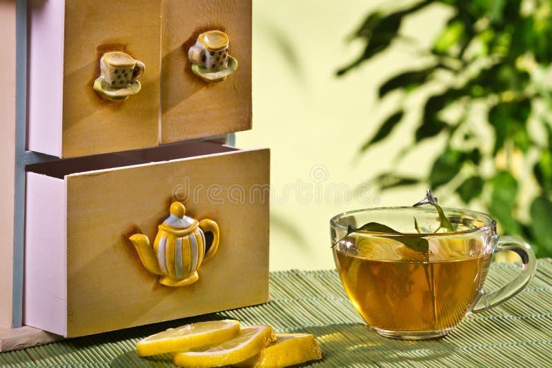Tea cupboard and hot tea and lemon royalty free stock photo