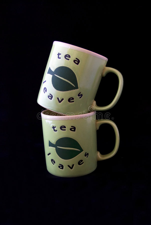 Tea cups. Two tea cups - yellow and green against black background royalty free stock photo