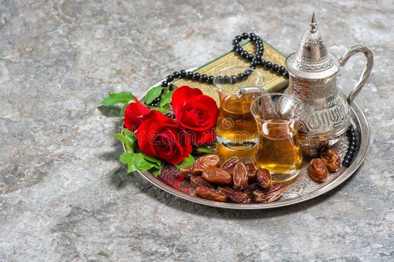 Tea, dates fruits, red rose flower, holy book quran and rosary. Islamic holidays decoration. Ramadan kareem. Eid mubarak. Oriental hospitality concept. Vintage royalty free stock photos