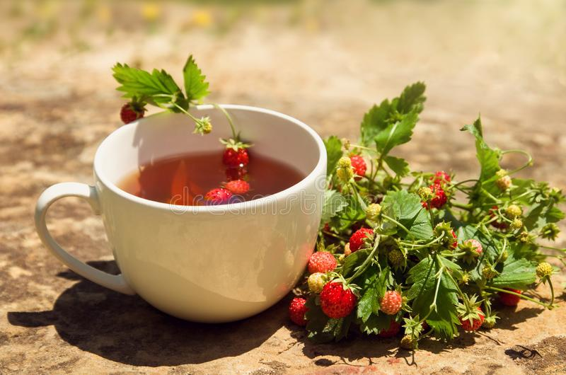 Tea drink in white Cup with wild wild wild strawberry berry on yellow stone background, scented Breakfast. Tea drink in white Cup with wild wild wild strawberry royalty free stock photography