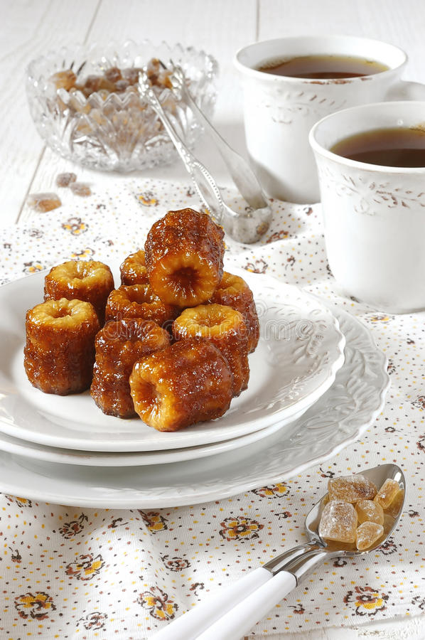 Tea-drinking: Canele - traditional dessert of French cuisine royalty free stock photo