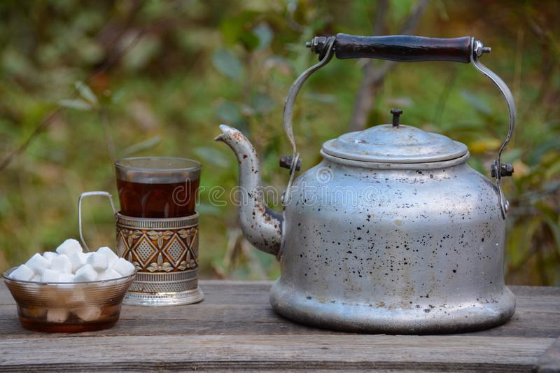 Tea drinking. Old grass, old teapot, sugar stock photography