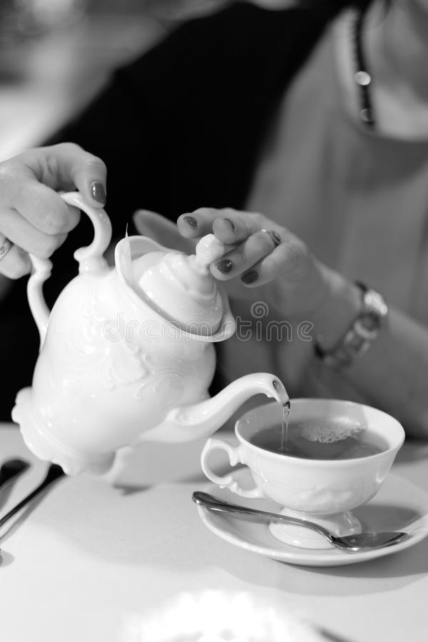 Tea drinking. A woman pours tea into a cup stock image