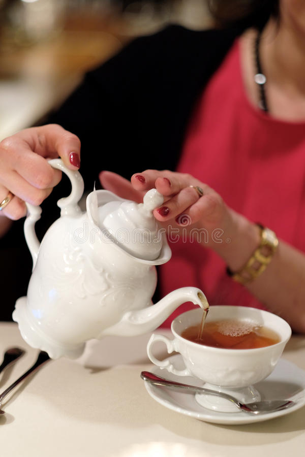 Tea drinking. A woman pours tea into a cup royalty free stock photos