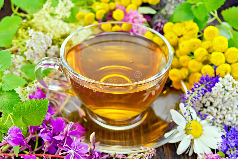 Tea from flowers in glass cup on dark board stock photo