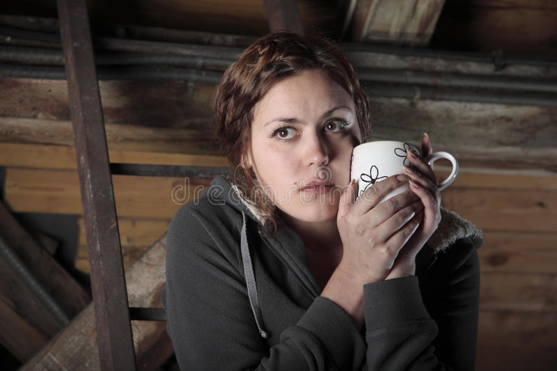 Tea on the garret. Young woman is drinking tea on the garret royalty free stock images