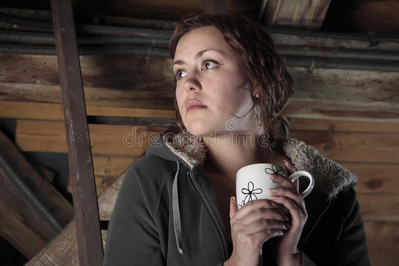Tea on the garret. Young woman is drinking tea on the garret stock image