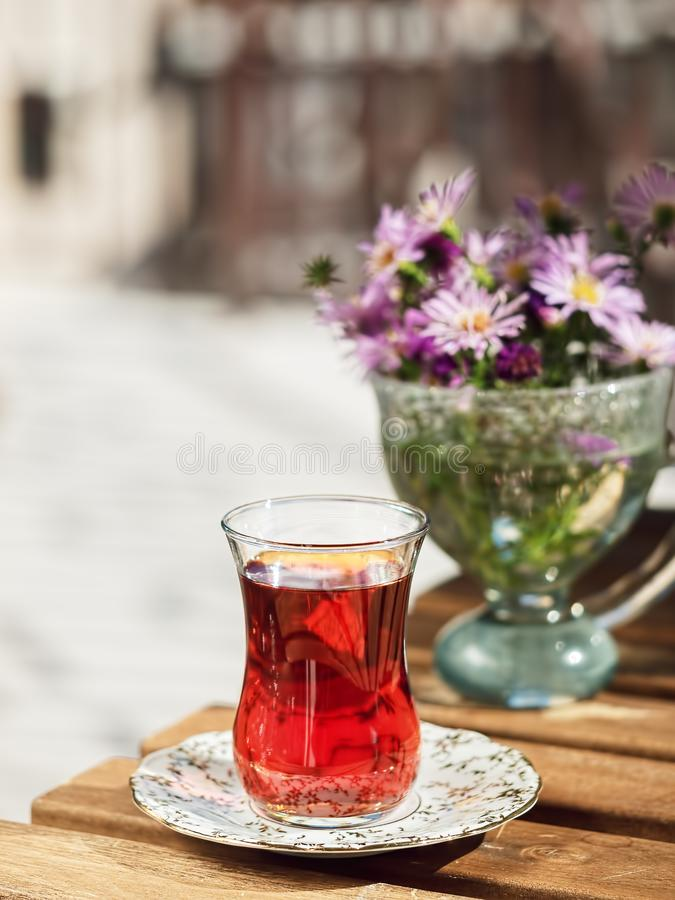 Tea in a glass of armudu on a saucer, located on a wooden table in the loggia. In the background are flowers . Bright sunny day. Close-up stock photo