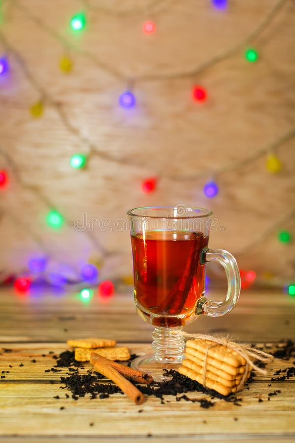 Tea in glass cup with cinnamon sticks and cookies with blurred light garland on background. Christmas concept royalty free stock photography