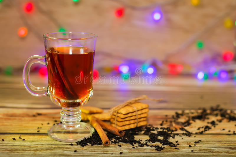 Tea in glass cup with cinnamon sticks and cookies with blurred light garland on background. Christmas concept stock photography