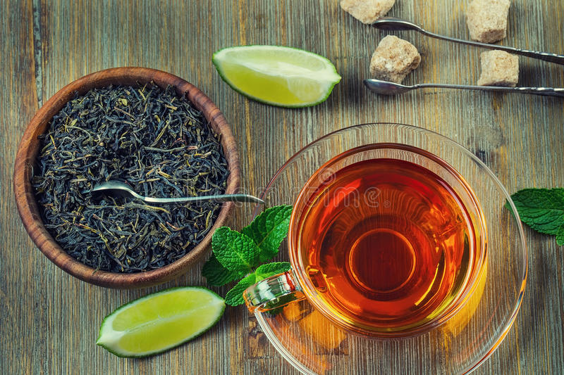 Tea in a glass cup, mint leaves, dried tea, sliced lime, cane sugar stock image