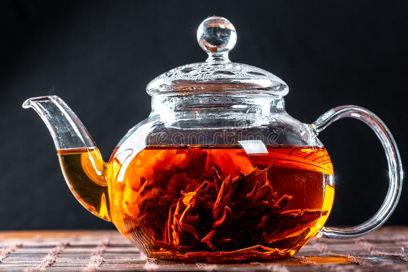 Tea in a glass teapot with a blooming large flower. Teapot with exotic green tea-balls blooms flower. Tea ceremony on a dark. Background royalty free stock image