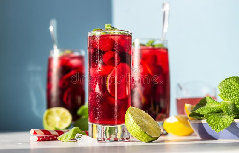Tea with hibiscus, berries raspberries and blackberries, mint, lime, lemon and ice in the sun with shadow. royalty free stock image
