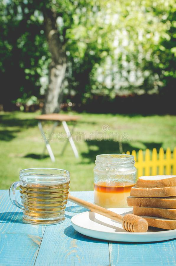 Tea with honey and the cut white pastries slices on a wooden blue table background. Tea with honey in a summer garden. Cup, design, nature, food, healthy royalty free stock photos