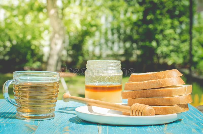 Tea with honey and the cut white pastries slices on a wooden blue table background. Tea with honey in a summer garden. Cup, design, nature, food, healthy royalty free stock images
