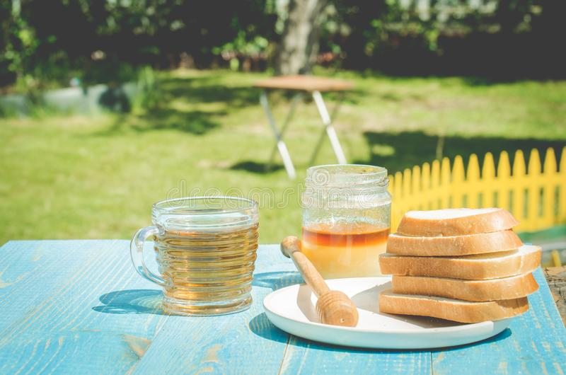 Tea with honey and the cut white pastries slices on a wooden blue table background. Tea with honey in a summer garden. Cup, design, nature, food, healthy stock photos