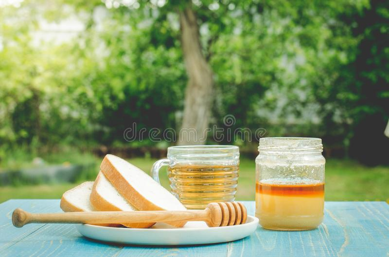 Tea with honey and the cut white pastries slices on a wooden blue table background. Tea with honey in a summer garden. Cup, design, nature, food, healthy stock photography