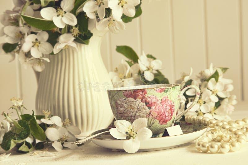 Tea kuper med äppleblomningar bordlägger på arkivbild