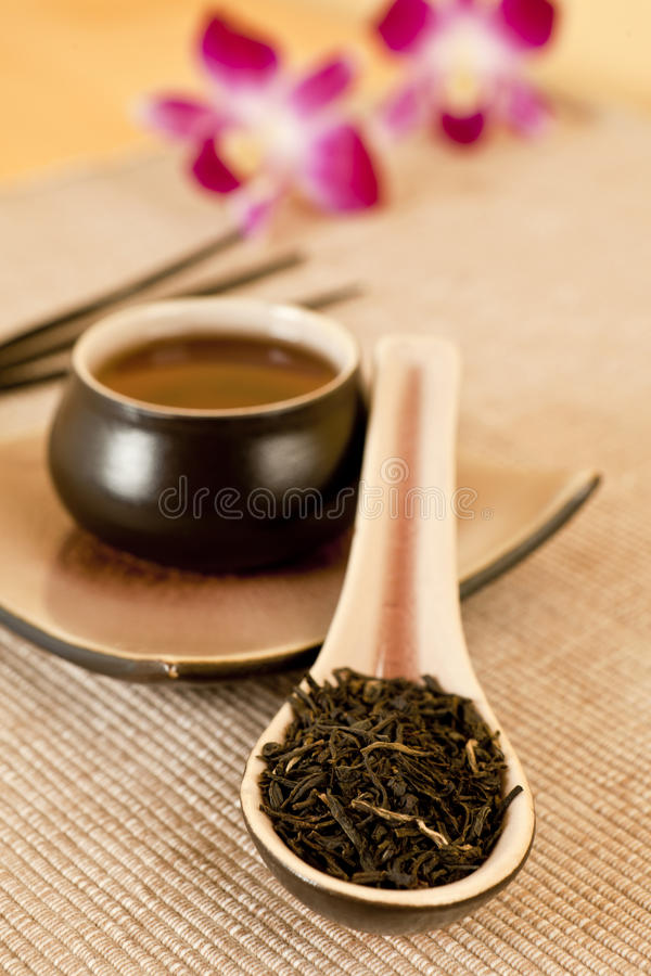 Tea leaves on a tea spoon. Cup of black tea, incense sticks and flowers in background stock photos
