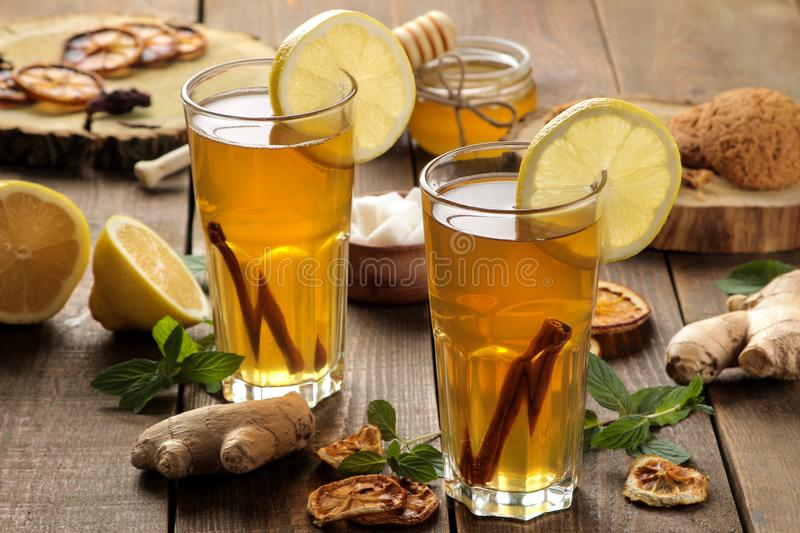 Tea with lemon and a cinnamon stick with ginger and mint in glass cups on a brown wooden table. a warming drink. Autumn or winter royalty free stock photography
