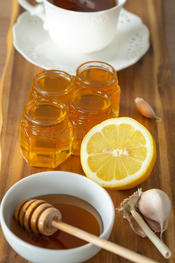 Tea, lemon, honey and garlic on a wooden counter, healthy and natural remedies for colds. Tea, lemon, honey and garlic on a wooden counter, health and natural royalty free stock photography