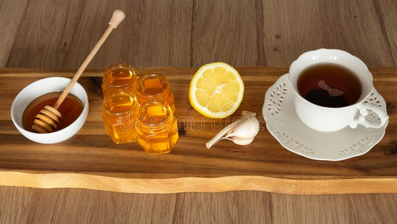 Tea, lemon, honey and garlic on a wooden counter, healthy and natural remedies for colds. Tea, lemon, honey and garlic on a wooden counter, health and natural stock images
