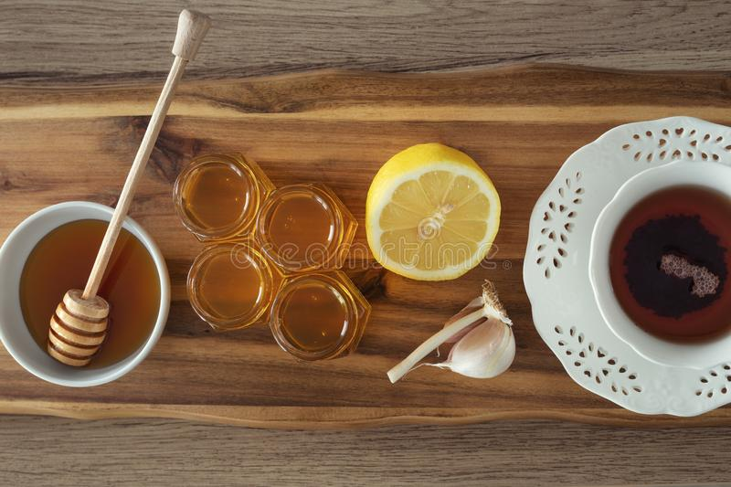 Tea, lemon, honey and garlic on a wooden counter, healthy and natural remedies for colds. Tea, lemon, honey and garlic on a wooden counter, health and natural royalty free stock photo