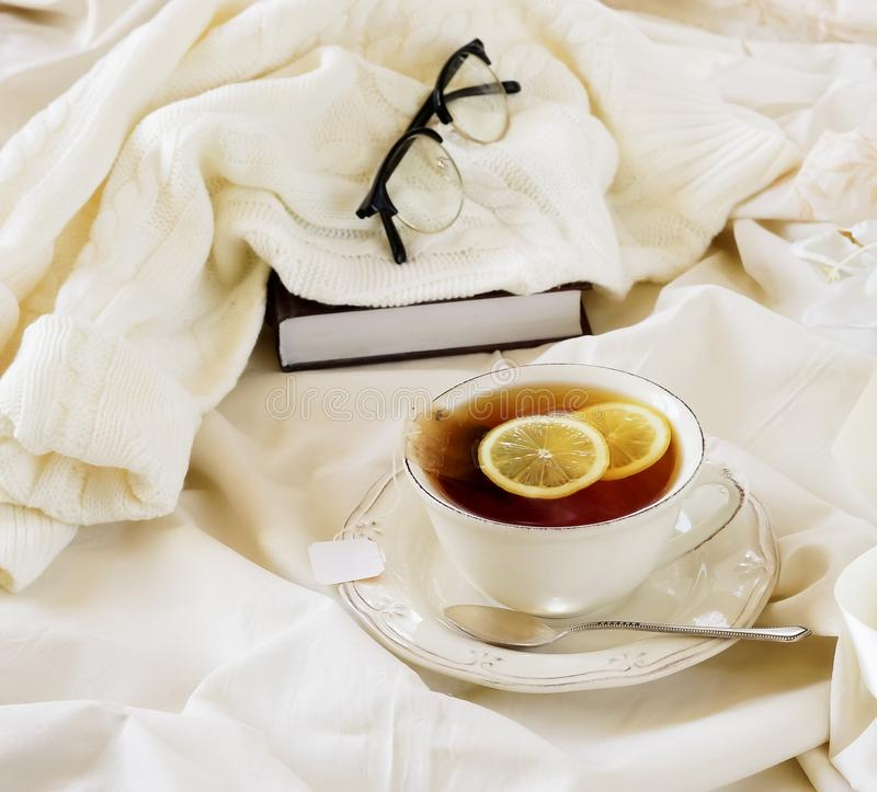 Lifestyle autumn winter composition. tea with lemon,. Tea with lemon, knitted sweater , glasses and book. home workspace in bed concept.warm beige pastel colors royalty free stock photo